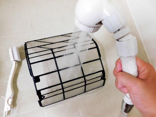 エアコンのフィルターを洗っている