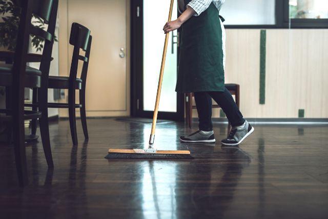 床にほうきで清掃